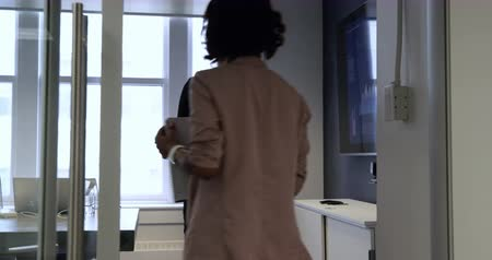 mounted : Rear view of two businesswomen working in a modern office walking into a meeting room and sitting down, joining a male colleague who is standing at a wall mounted monitor and talking on a smartphone