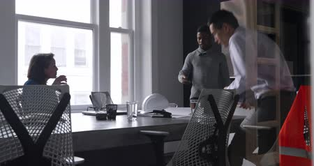 csatlakozott : Side view of a Caucasian businesswoman sitting at a desk during a meeting with an African American man standing using a smartphone, joined by a mixed race man who sits down and uses a tablet computer,  all three looking at architectural plans together and