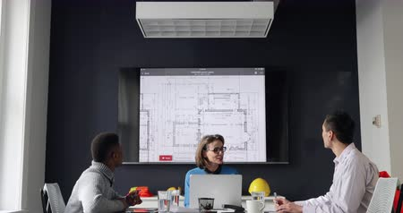 mounted : Front view of a Caucasian woman using a laptop, a mixed race man and an African American man sitting at a table during a meeting in a modern office, talking and turning to look at an architectural drawing on a wall mounted screen together