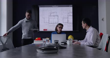 csatlakozott : Front view of a Caucasian woman using a laptop sitting and talking with a mixed race man during a meeting in a modern office, they are joined by an African American man who sits down with them, an architectural drawing is displayed on a wall mounted scree Stock mozgókép