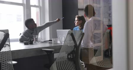 smíšené rasy osoba : Side view of a Caucasian woman using a laptop, a mixed race man and an African American man sitting at a table during a meeting in a modern office, talking and looking at a wall mounted screen together. Seen through a glass wall with reflections