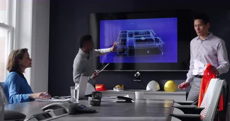 mounted : Side view of a Caucasian woman sitting at a desk at a meeting in a modern office with an African American man standing holding a tablet computer and presenting a 3d architectural plan on a wall mounted monitor, they are joined by a mixed race man carrying