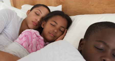 v řadě : Front view close up of an African American woman and her young son and daughter lying asleep together in a row in her bed, slow motion