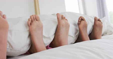 羽毛布団 : Front view close up of the feet of an African American woman and her young son and daughter sticking out of the covers as they lie asleep together in a row in her bed, slow motion 動画素材