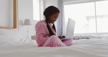 pigtailler : Side view of a young African American girl at home, sitting on a bed wearing a pink clothes using a laptop computer, slow motion