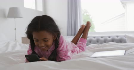 pigtailler : Front view close up of a young African American girl at home, lying on a bed, using a smartphone and smiling, with a laptop beside her on the bed, slow motion