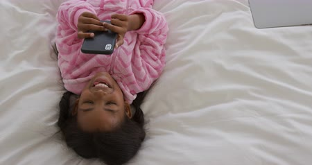 pigtailler : High angle view of a young African American girl at home, lying on her back on a bed wearing a onesie, using a smartphone and smiling, slow motion