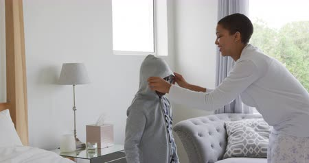 juntar : Side view of an African American woman at home in a bedroom, helping her young son get dressed, putting on his hoodie, talking to him and smiling, slow motion