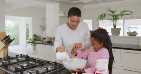 korsó : Front view of a smiling African American woman and her young daughter at home in the kitchen making pancakes, adding the ingredients into a mixing bowl, the mother pouring milk and the girl stirring, slow motion Stock mozgókép