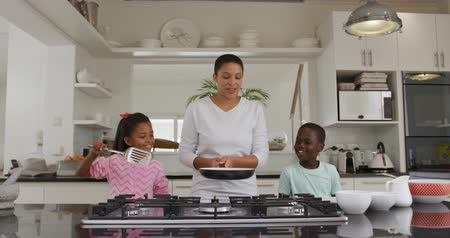 ailelerin : Front view of an African American woman and her young son and daughter at home in the kitchen making pancakes, the mother holding a frying pan over the hob and tossing a pancake, while her children watch, smilng, slow motion Stok Video