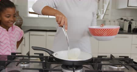 naleśnik : Front view mid section of an African American woman at home in the kitchen putting pancake mixture into a frying pan with a ladle, watched by her young daughter and son, slow motion