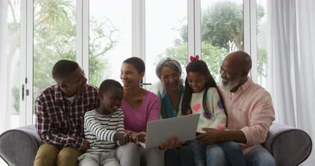 socialising : Front view of six members of multi-generation African American family at home in the sitting room sitting on a sofa together, smiling and looking at a laptop computer, the granddaughter sitting on the knee of her granddad and the grandson sitting between