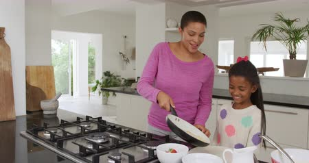 bliskosc : Front view of a smiling African American woman and her young daughter at home in the kitchen making food, the mother serving to a plate from a frying pan while her daughter watches, slow motion