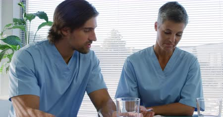 скрабы : Front view close up of a Caucasian male and female healthcare worker wearing scrubs, sitting at a table talking and making notes in an office at a hospital