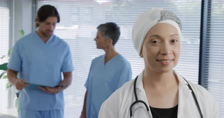 turban : Portrait close up of a mixed race female healthcare worker wearing a lab coat and a turban smiling to camera, with two colleagues talking in the background, slow motion