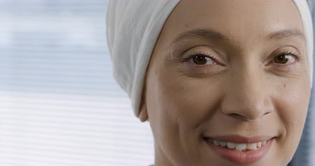 turban : Head shot of a mixed race female healthcare worker wearing a turban looking to camera smiling, in front of the window in an office at a hospital