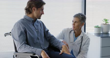 recovering : Front view tilt shot of a Caucasian female doctor kneeling beside a Caucasian male patient in a wheelchair and talking to him, during a consultation at a hospital