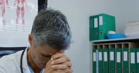 clasped : Front view close up of a Caucasian female doctor sitimg at a desk, resting her head in her hands and looking up in thought, in an office at a hospital Stock Footage