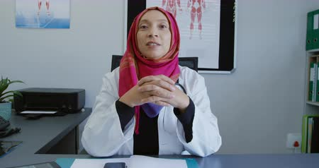 clasped : Front view of a mixed race female doctor wearing a lab coat and a pink hijab, sitting behind a desk in a medical office talking to camera
