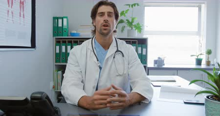clasped : Front view of a Caucasian male doctor wearing a lab coat sitting behind a desk in a medical office talking to camera Stock Footage