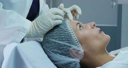 čelo : Side view of a Caucasian woman wearing a cap and lying down while a doctor gives botox injections to her forehead at a clinic Dostupné videozáznamy