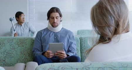 gryf : Over the shoulder view of a Caucasian man wearing a neck brace sitting in a hospital waiting room using a tablet computer, with a female patient in the foreground and another male patient waiting in the background