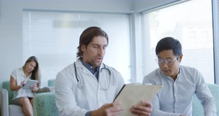 doktor : Front view of a Caucasian male doctor walking into a hospital waiting room, shaking hands and sitting down to talk with an Asian male patient and showing him some documents, a female patient sits in the background