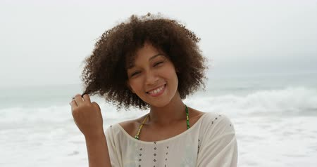roupa de praia : Portrait close up of an African American woman with short curly hair standing on a beach with the sea behind her, playing with her hair and smiling to camera, slow motion Vídeos