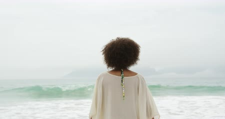 пляжная одежда : Rear view of an African American woman with short curly hair, standing on a beah facing teh sea and raising her arms in the air, slow motion