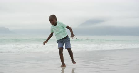 roupa de praia : Front view of a barefoot young African American boy wearing shorts and a t shirt doing cartwheels along a beach by the sea, slow motion