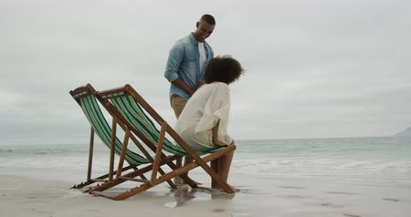 deck chairs : Side view of an African American couple on a beach, sitting down on deck chairs by the sea to relax together, slow motion