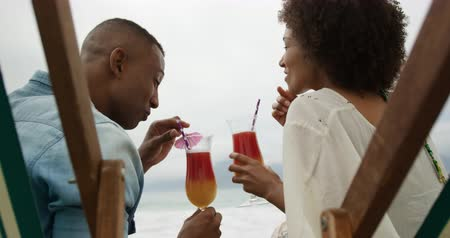 пляжная одежда : Rear view close up of an African American couple on a beach by the sea, sitting on deck chairs, drinking fruity cocktails with straws and laughing, slow motion