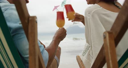 deck chairs : Rear view close up of an African American couple on a beach by the sea, sitting on deck chairs, making a toast and drinking fruity cocktails, slow motion