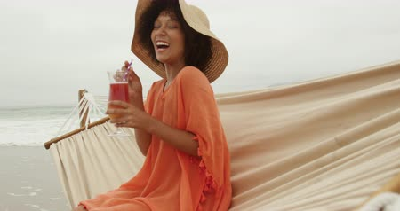 sunhat : Side view of an African American woman on a beach by the sea, wearing a sunhat and drinking a cocktail sitting on a hammock smiling, slow motion