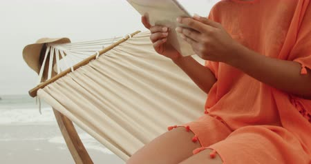 пляжная одежда : Side view close up of an African American woman on a beach by the sea, sitting on a hammock using a tablet computer and smiling, slow motion