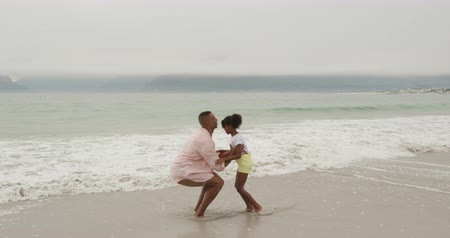 пляжная одежда : Side view of an African American man standing on a beach by the sea, throwing his young daughter in the air and catching her, slow motion