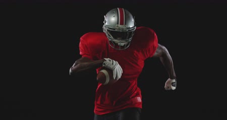 kask : Front view of an African American male American football player wearing a team uniform, pads and a helmet, running forward with a football in his hand, slow motion Stok Video