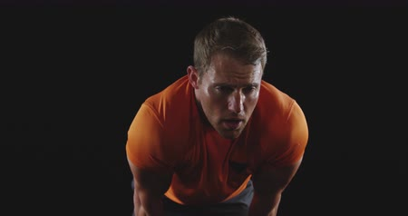 perspiring : Front view close up of a muscular Caucasian man wearing sports clothes leaning forward, recovering after a work out, slow motion Stock Footage
