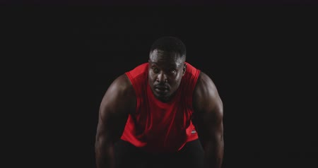 perspiring : Front view close up of a muscular African American man wearing sports clothes leaning forward, recovering after a work out, slow motion