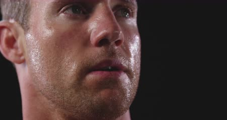 perspiring : Head shot of a Caucasian male athelete sweating after a work out, turning his head and looking away, slow motion Stock Footage
