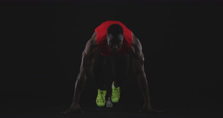 velocista : Front view close up of a muscular African American male runner using starting blocks at the beginning of a race, slow motion Archivo de Video