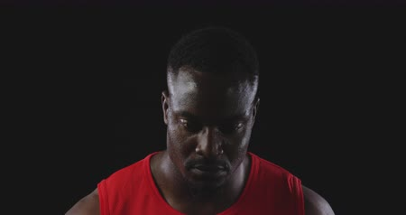 perspiring : Portrait of an African American male athlete sweating after a work out, raising his head and looking to camera, slow motion
