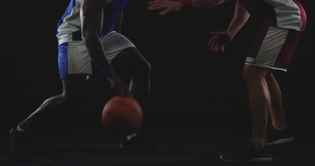 blocage : Side view low section of a Caucasian male basketball player wearing team colours preparing to block a ball being dribbled by an African American male player on the opposing team, slow motion Vidéos Libres De Droits