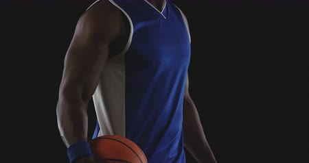trikot : Portrait of a muscular African American male basketball player wearing team colours holding a basketball in one hand against his hip and turning to look to camera, slow motion