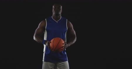 vest : Portrait of a muscular African American male basketball player wearing team colours holding a basketball in two hands in front of him and looking to camera, slow motion