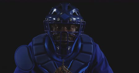 guantone : Front view close up of an African American male baseball catcher, wearing a team uniform, protective clothing and a helmet, catching a pitch with his mitt, slow motion