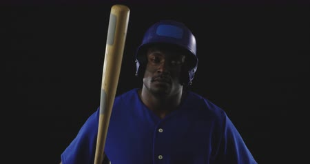 jarse : Portrait close up of an African American male baseball hitter wearing a team uniform and a helmet, looking to camera and resting a baseball bat on his shoulder, slow motion Stok Video