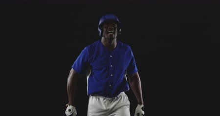 jarse : Front view of an African American male baseball hitter wearing a team uniform and a helmet, swinging a baseball bat and celebrating a victory with shouts and clenched fists, slow motion