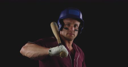 bat : Side view close up of a Caucasian male baseball hitter wearing a team uniform and a helmet, with eye black under his eyes, turning to face camera with a baseball bat resting on his shoulder, slow motion