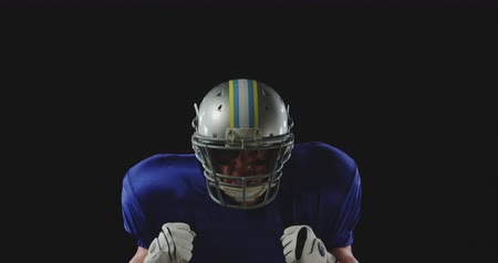 кулак : Portrait close up of a Caucasian male American football player wearing a team uniform, pads and a helmet, raising fists in celebration of a victory, slow motion Стоковые видеозаписи